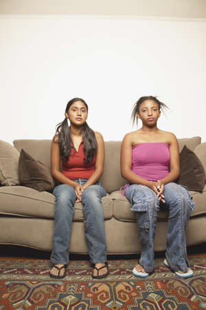 Portrait of two teenage girls sitting on a couch LANG_EVOIMAGES