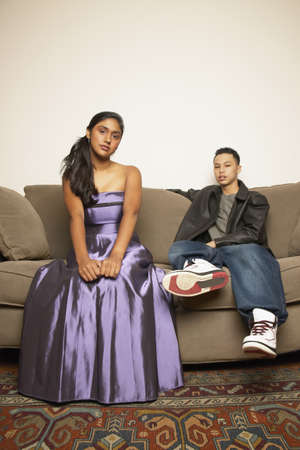 Portrait of a teenage couple sitting on a couch LANG_EVOIMAGES