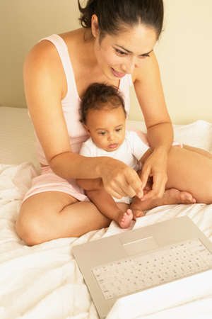 spanish ethnicity: Young woman sitting on a bed with a baby in front of a laptop