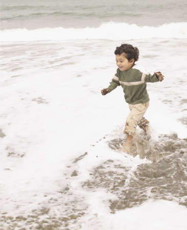 freewill: Young boy running in the water on the beach