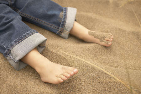 Legs of a young boy lying on sand Stock Photo - 16045207
