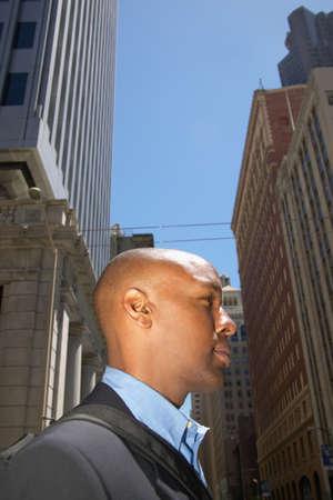 hauteur: Mid adult businessman standing outdoors looking ahead