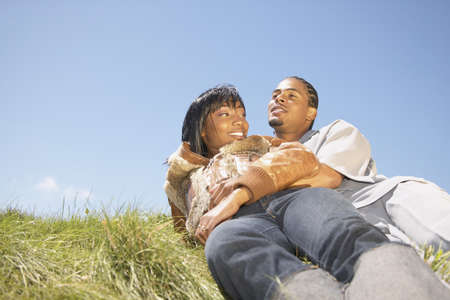 informant: Low angle view of a young couple lying in grass LANG_EVOIMAGES