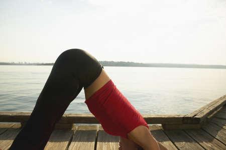 leeway: Young woman performing yoga outdoors