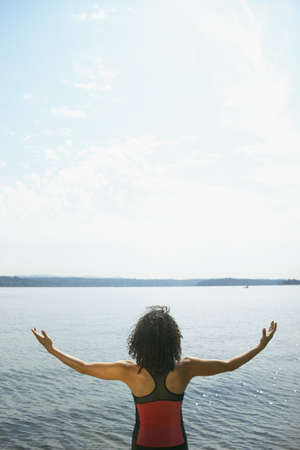 restfulness: Rear view of a young woman standing in front of a lake with her arms outstretched LANG_EVOIMAGES