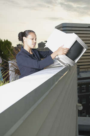 prickling: Young businesswoman standing holding a computer monitor over a wall