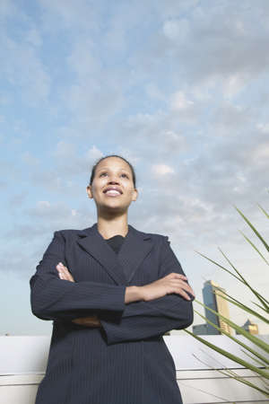 effrontery: Low angle view of a young businesswoman standing with arms folded