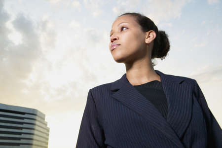 credence: Low angle view of a young businesswoman looking sideways