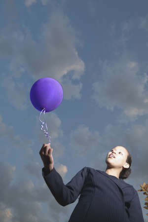 Low angle view of young businesswoman holding a balloon Stock Photo - 16045231