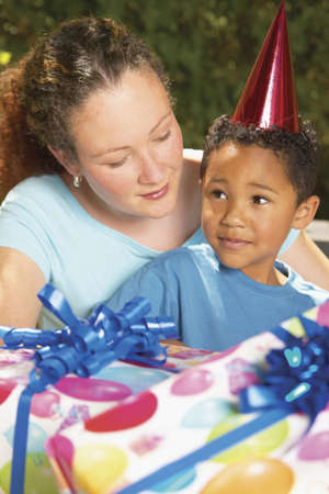 Mid adult woman sitting with a young boy holding presents