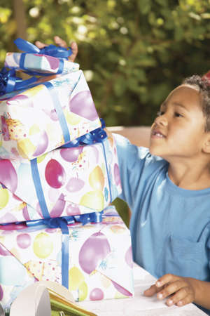 Side profile of a young boy standing next to a stack of presents LANG_EVOIMAGES