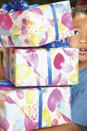 Young boy carrying a stack of presents