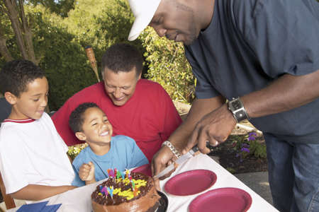 Mid adult men and two young boys in front of a birthday cake
