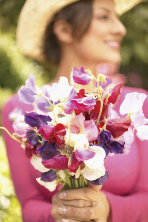 Young woman holding a bunch of flowers in a garden Stock Photo - 16045242