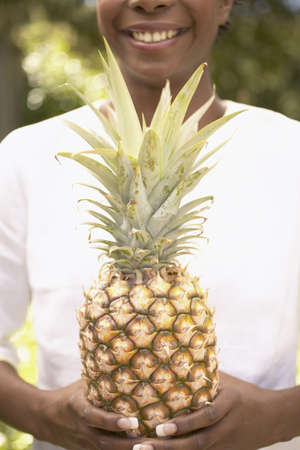 chirpy: Woman holding a pineapple at a garden