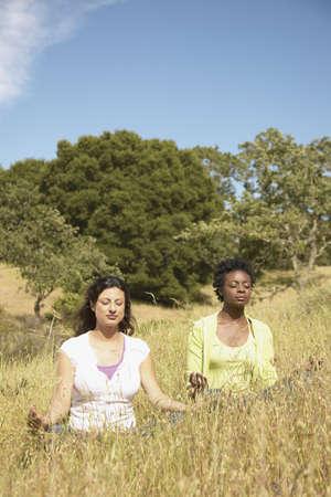 pragmatism: Young woman meditating on a hillside