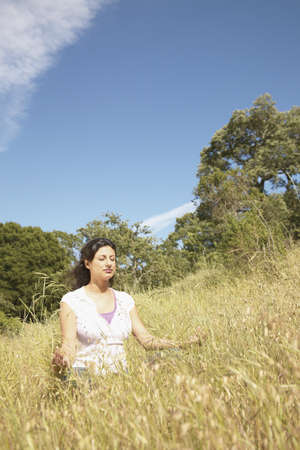 pragmatism: Woman meditating on a hillside LANG_EVOIMAGES
