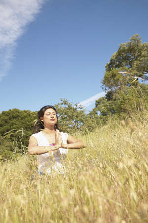 naivete: Young woman meditating on a hillside