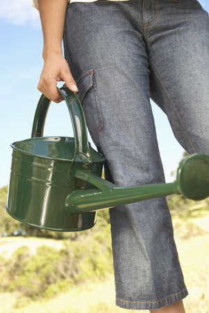 pragmatism: Low section view of young woman holding a watering can