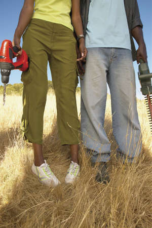 Lower section of a young couple standing holding a drill machine and a saw Stock Photo - 16045270
