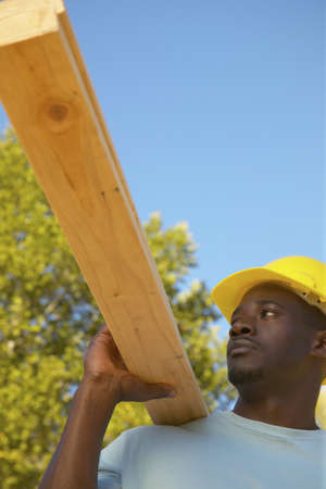 Young man holding a wooden plank on his shoulder Stock Photo - 16045271