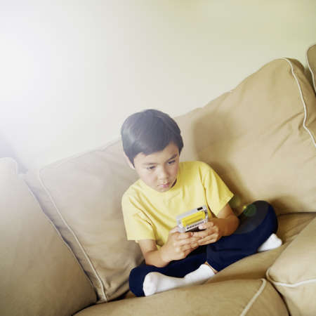 Young boy sitting on a couch playing a video game