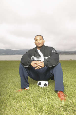 Young man player sitting on football in ground Stock Photo - 16045278