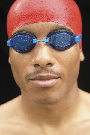 effrontery: Young male swimmer wearing a swimming cap and swimming goggles LANG_EVOIMAGES