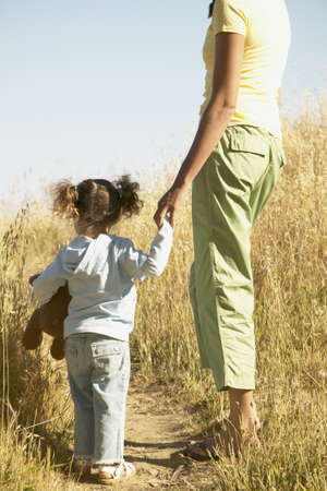 mothering: Rear view of a young woman holding a young girls hand standing in a field of tall grass