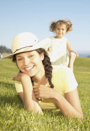 joyousness: Young woman lying on the grass with a young girl behind