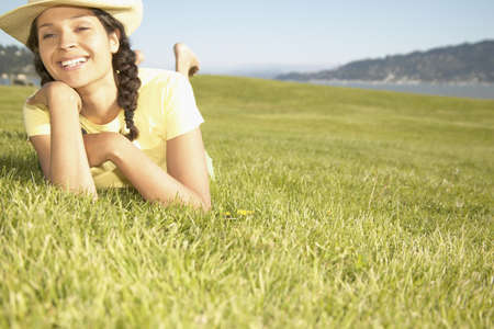 freewill: Young woman lying on grass smiling LANG_EVOIMAGES
