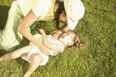 joyousness: High angle view of a young woman playing with a young girl on the grass LANG_EVOIMAGES