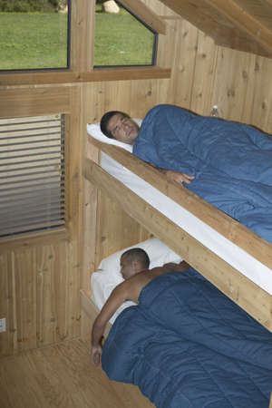 Two young men sleeping in bunk beds
