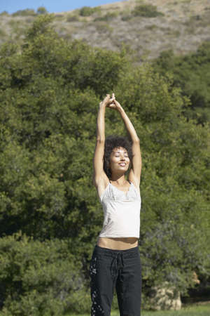 freewill: Young woman standing outdoors with her hands raised LANG_EVOIMAGES