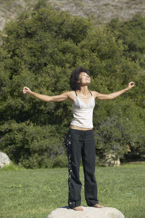 freewill: Young woman standing with on a rock outdoors with her arms stretched out LANG_EVOIMAGES