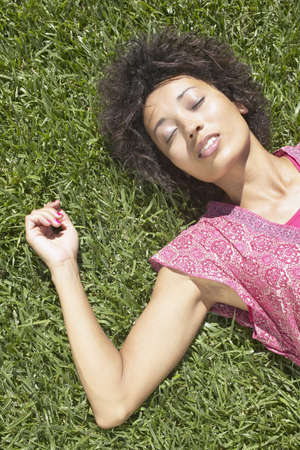 Young woman lying on the grass Stock Photo - 16045295