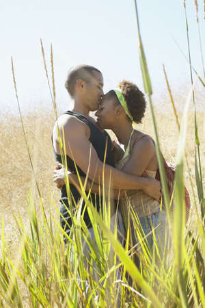 human evolution: Young couple standing in tall grass holding each other