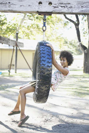 joyousness: Portrait of a young woman sitting on a tire swing