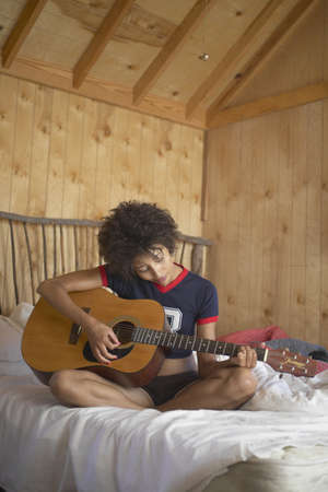 Young woman sitting on abed playing the guitar Stock Photo - 16045304