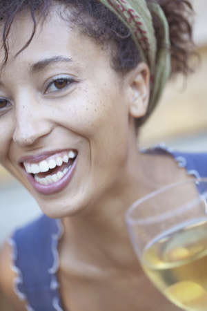 joyousness: Portrait of a young woman smiling holding a wine glass
