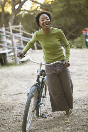 absolution: Young woman smiling holding a bicycle LANG_EVOIMAGES