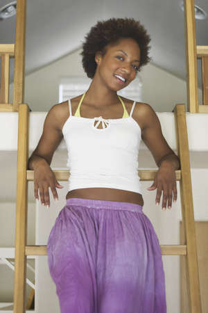 effrontery: Portrait of young woman smiling sitting on a step ladder