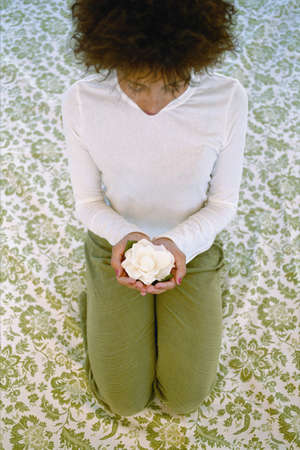 kneel down: High angle view of a mid adult woman kneeling holding a flower LANG_EVOIMAGES