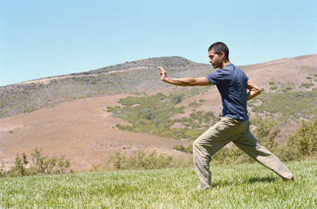 informant: Mid adult man practicing martial arts on a lawn