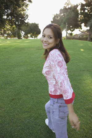 Rear view of a young woman walking on a lawn looking back smiling Stock Photo - 16045339