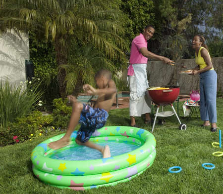 Family having a barbeque on a lawn with a young boy jumping into a pool