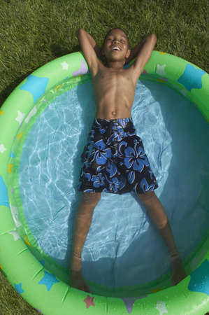 blase: High angle view of a young boy lying in pool