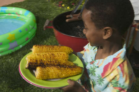 Young boy holding a plate of barbequed corn Stock Photo - 16045346