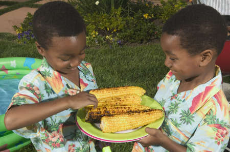 Two young boys holding a plate of corn Stock Photo - 16045347