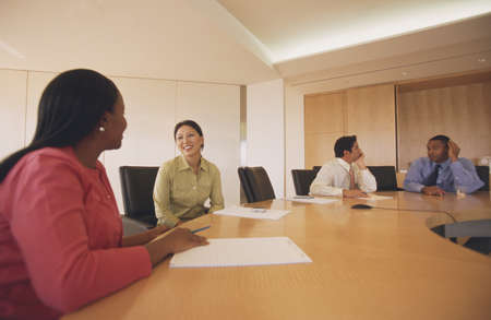 Business executives seated at a table in a meeting LANG_EVOIMAGES